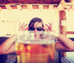 Woman Peaking Over Beer Glass
